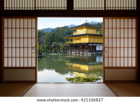 View of a beautiful Japanese golden temple and pond garden seen through open rice paper doors - stock photo