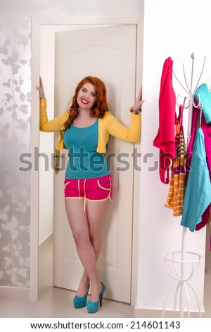 View of a beautiful redhead girl with colorful clothes in her bedroom. - stock photo