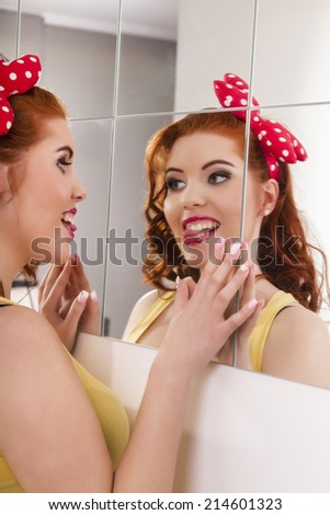 View of a beautiful redhead girl with colorful pinup clothes next to a mirror wall. - stock photo