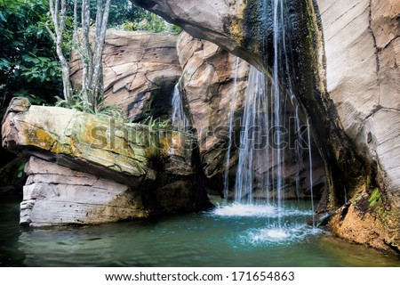 View of a beautiful relaxing tropical waterfall pouring down in a small lake formed out of limestone - stock photo