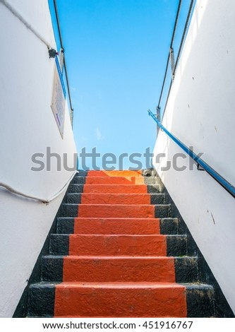 view of a black and red staircase reaching blue sky - stock photo