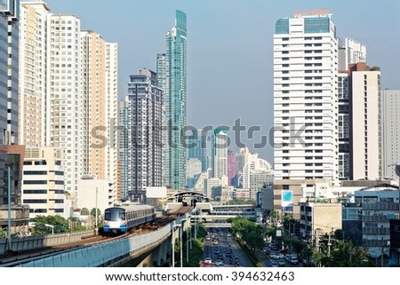 View of a BTS skytrain traveling on elevated metro system between high rise skyscrapers in Bangkok downtown on a beautiful sunny day ~ Scenery of Bangkok, the fast developing capital city of Thailand - stock photo