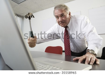 View of a business man trying to hit a laptop with a hammer. - stock photo