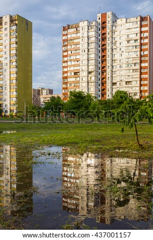 View of a city after a heavy rain. High-rise buildings are reflected in the puddles on a background cloudy sky, at the moment when the low evening sun looked out and lit them. - stock photo