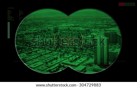 view of a city in the crosshairs night vision device of terrorism  - stock photo