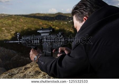 View of a contracted type killer agent wandering with a long jacket and machine gun. - stock photo