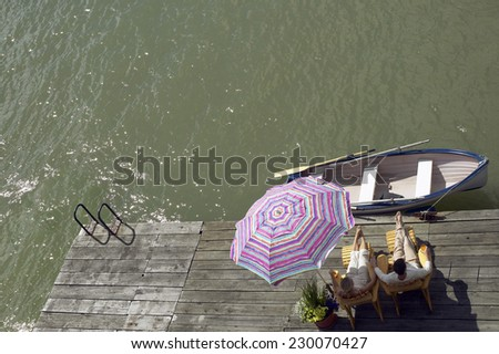 View of a couple lounging in the sun viewed from a balcony - stock photo
