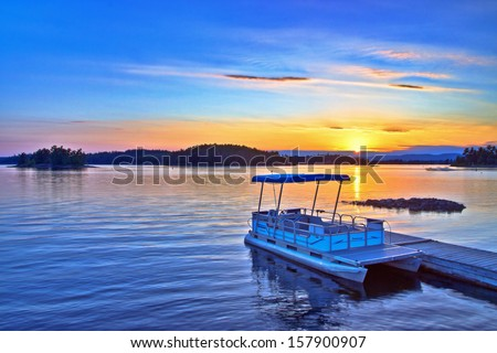 View of a docking yacht on a lake during sunset - stock photo