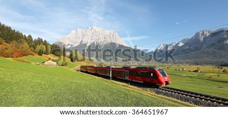 View of a fast train traveling through green fields with magnificent Mountain Zugspitze in the background on a crisp sunny day in Lermoos, Tirol, Austria ~ Brisk autumn scenery of Tyrolean countryside - stock photo