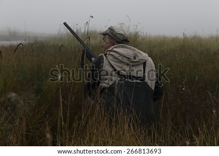 view of a gamekeeper in autumn fog. - stock photo