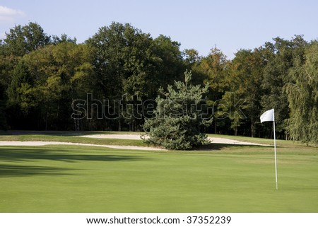 View of a golf course - Green with a white flag - stock photo