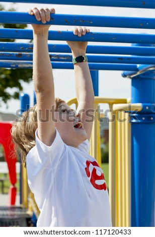 View of a happy elementary boy crossing monkey bar, - stock photo
