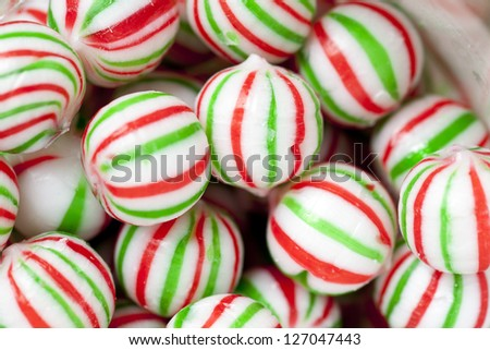 View of a heap of colorful candies with red and green stripes. - stock photo