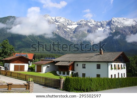 View of a house with the Alps Mountains in the background with sunny blue sky in Austria - stock photo