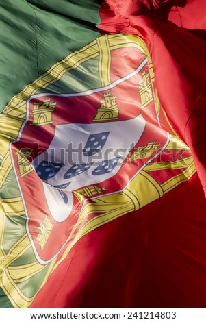 View of a huge portuguese flag flapping in the wind. - stock photo