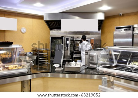 View of a kitchen with baker preparing breads and baguettes in a cafeteria - stock photo