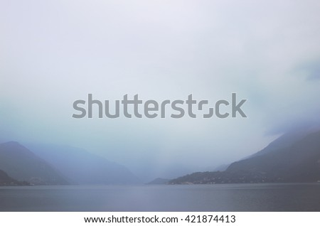 View of a lake and hills in a gloomy morning - stock photo