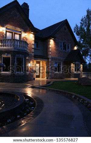 view of a large luxurious home in the evening after a light rain with the house lit up - stock photo