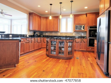 View of a large upscale kitchen with hardwood floors and modern fixtures. Horizontal format. - stock photo