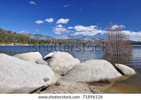 View of a lone barren tree and some boulders along the shoreline of Hemet Lake. - stock photo