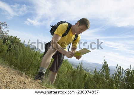 View of a man consulting a map whilst hiking in a rural area - stock photo