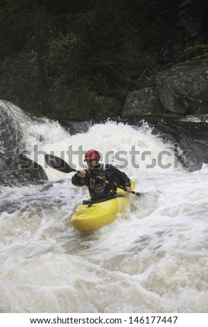 View of a man kayaking in rough river - stock photo