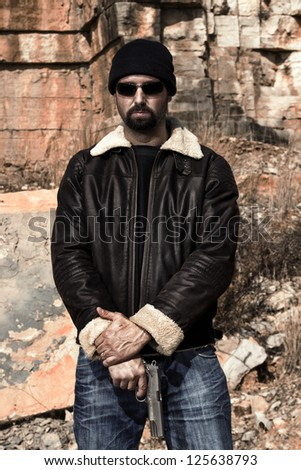 View of a man with a gun in jeans and jacket on a stone quarry. - stock photo