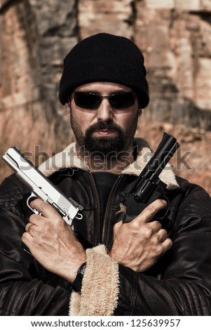 View of a man with two guns on a stone quarry. - stock photo