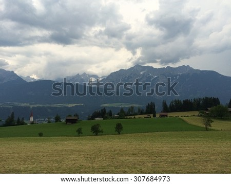 View of a meadow and mountains - stock photo