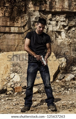 View of a menacing man preparing a handgun in a black shirt and dark shades on a stone quarry. - stock photo