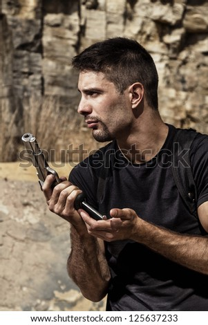 View of a menacing man reloading a handgun in a black shirt and dark shades on a stone quarry. - stock photo