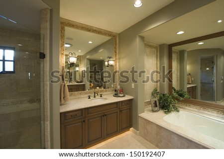 View of a modern bathroom with bathtub and square mirror at washbasin in home - stock photo
