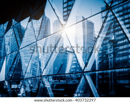 View of a modern glass skyscraper reflecting the blue sky,blue toned image. - stock photo