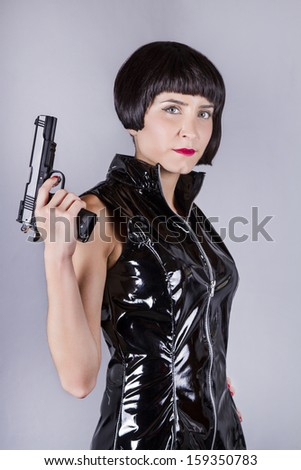 View of a modern pin-up girl with dark shinny dress holding a gun. - stock photo