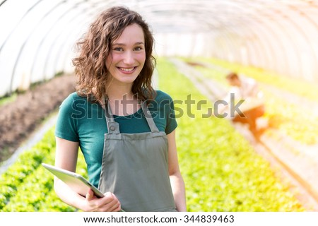 View of a Portrait of an attractive farmer in a greenhouse using tablet - stock photo