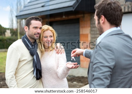 View of a Real estate agent delivers keys to young atractive couple - stock photo