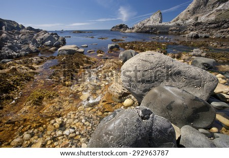 View of a rocky beach on a summer day on the rugged west coast of  Donegal Ireland with blue sky and isolated clouds - stock photo
