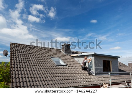 View of a rooftop with a working roofer assembling pieces to the dormer wall - stock photo