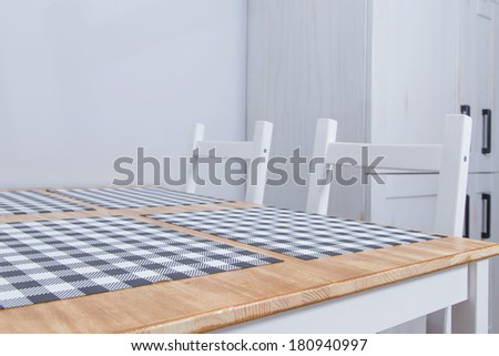 View of a rustic kitchen table with white chairs - stock photo