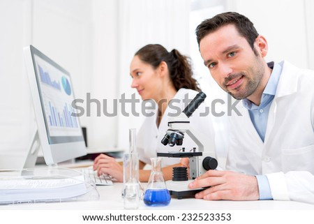 View of a Scientist and her assistant in a laboratory - stock photo