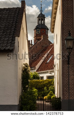 View of a small street and church in the Dutch city Buren. - stock photo