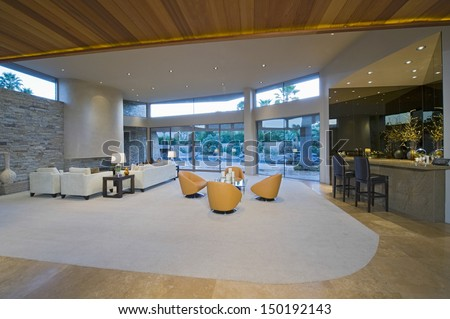 View of a spacious and modern living room by bar area with porch view - stock photo