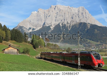 View of a train traveling through green fields with Mountain Zugspitze in the background on a beautiful sunny day in Lermoos, Tirol Austria ~ Magnificent autumn scenery of idyllic Tyrolean countryside - stock photo
