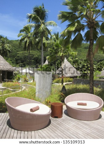 View of a tropical resort spa with relaxing chairs, mountain and palm trees. Small huts and lush green forest in the Seychelles - stock photo