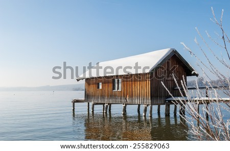"""View of a typical old boathouse at the lake """"Ammersee"""" in South Bavaria in the wintertime - stock photo"""
