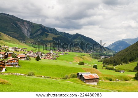 View of a typical Swiss village in a valley. Swiss Alps - stock photo