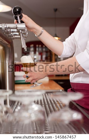 View of a waitress or female bartender pouring a pint of fresh draft beer behind the counter from a row of metal taps or spigots - stock photo