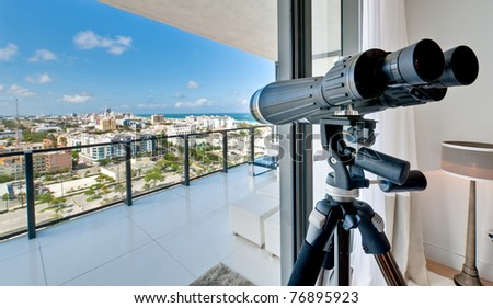 View of a window of a luxury apartment with binoculars. View of Miami Beach. - stock photo