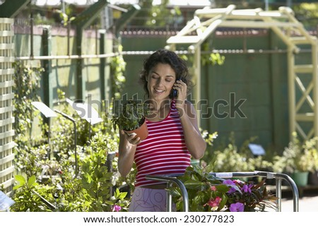 View of a woman talking on her mobile phone as she browses the plants at a gardening store - stock photo