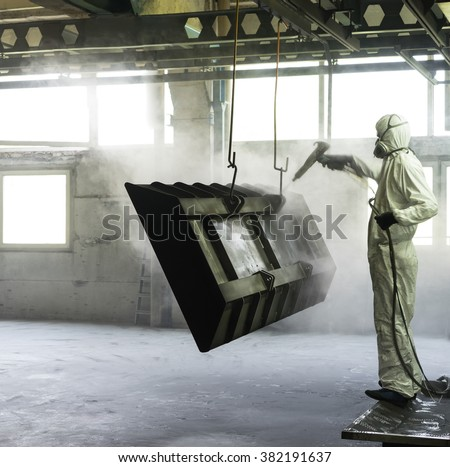 view of a worker wearing a full white protective suit and breathing mask, sand blasting a metal crate hung from a metal beam in the ceiling of an industrial hall - stock photo